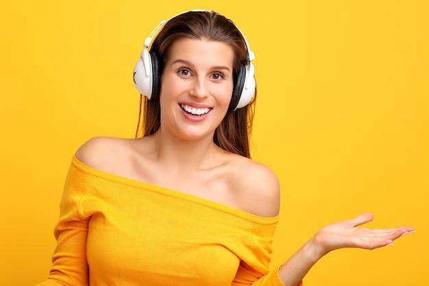 Schöne frau, die über gelb musik auf dem handy hört