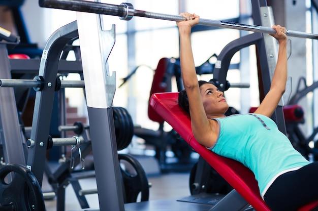 Schöne frau, die übungen mit langhantel auf der bank im fitness-studio macht