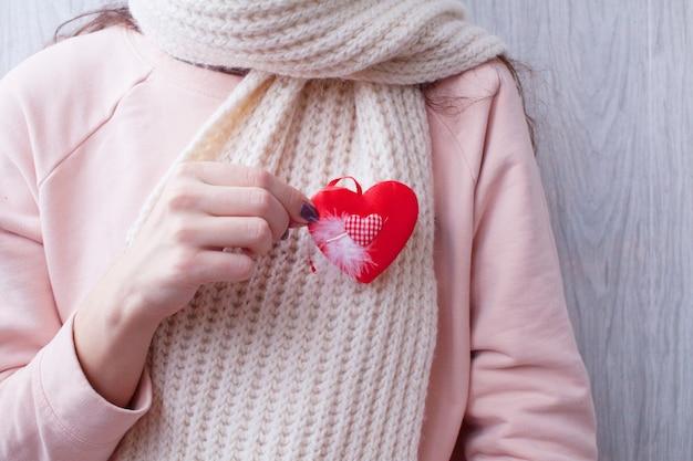 Schöne frau, die valentinstag-papierherzkarte hält