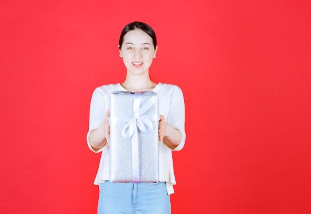Schöne frau, die verpackte geschenkbox hält und auf roter wand steht