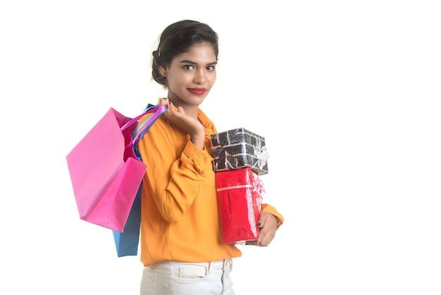 Schöne frau, die viele einkaufstaschen und geschenkbox auf einer weißen wand trägt.
