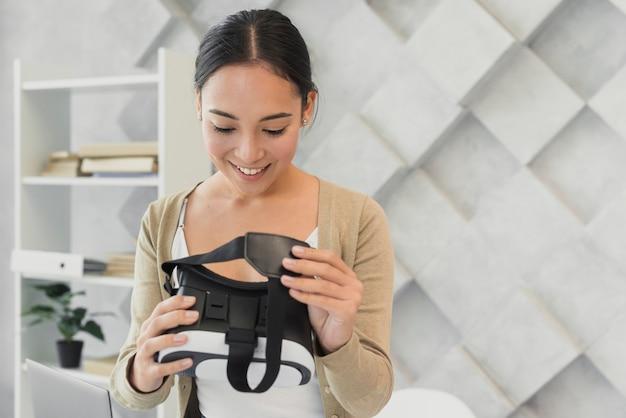 Schöne frau, die virtuellen kopfhörer betrachtet