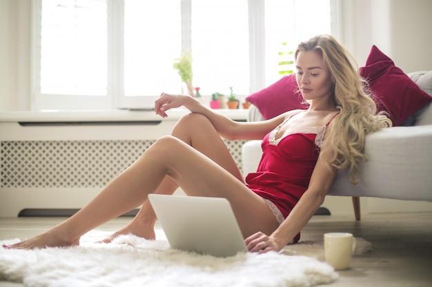Schöne frau, die von zu hause aus mit ihrem laptop arbeitet