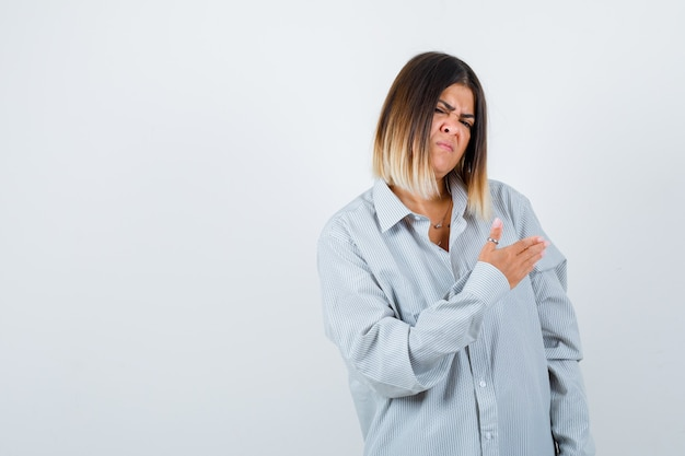 Schöne frau, die vorgibt, etwas im hemd zu zeigen und angewidert aussieht. vorderansicht.