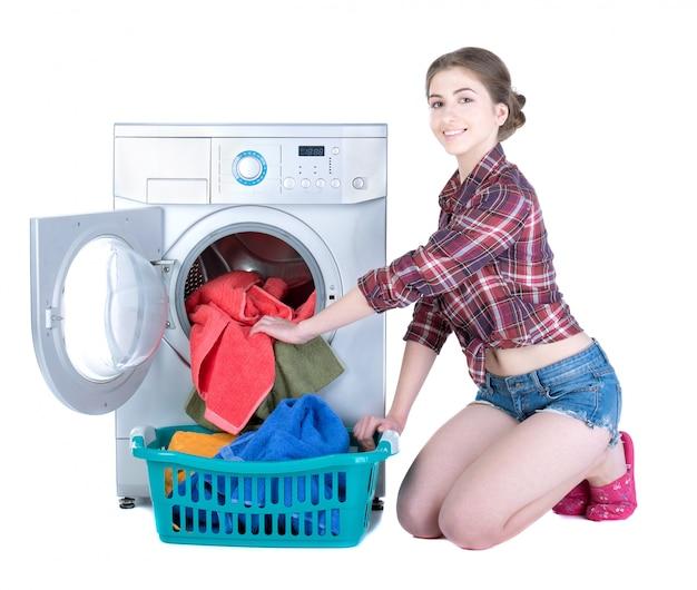Schöne frau, die wäscherei in der waschmaschine tut.