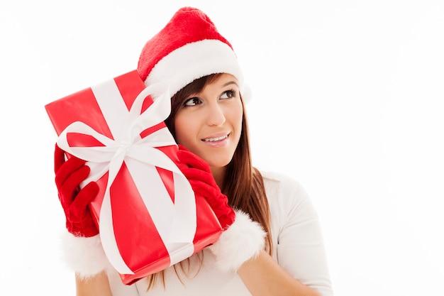 Schöne frau, die weihnachtsgeschenk schüttelt