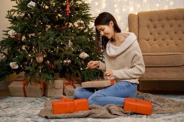 Schöne frau, die weihnachtsgeschenkbox öffnet, sitzt auf boden nahe festlichem baum zu hause
