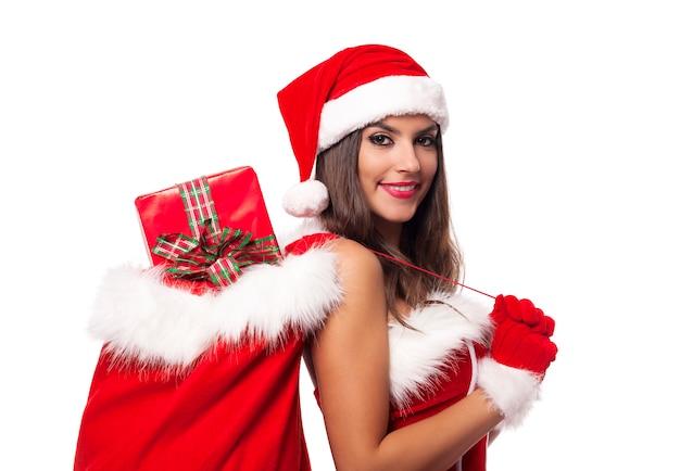 Schöne frau, die weihnachtsmannkleidung trägt, die sack voll von weihnachtsgeschenken hält