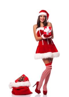 Schöne frau, die weihnachtsmannkleidung trägt, die weihnachtsgeschenk hält