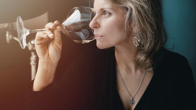 Schöne frau, die wein im restaurant trinkt