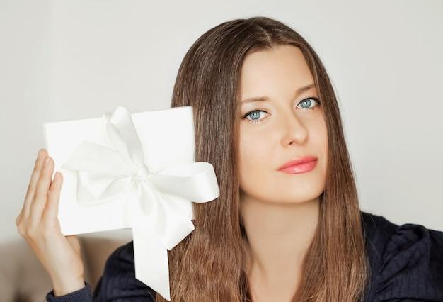 Schöne frau, die weiße geschenkbox, schönheitsporträt und luxusgeschenkkonzept hält