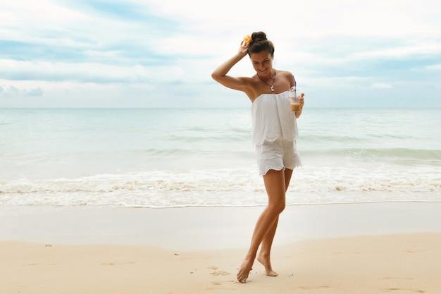 Schöne frau, die weißen overall trägt, geht am strand mit einem glas eiskaffee spazieren