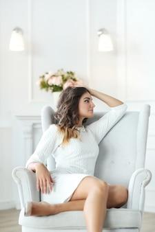 Schöne frau, die weißes kleid trägt und im weißen sessel sitzt