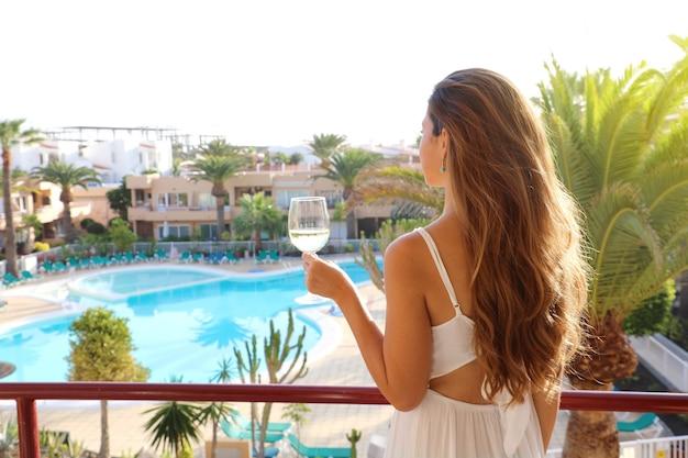 Schöne frau, die weißwein auf der außenterrasse des resorts trinkt