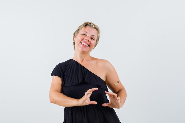 Schöne frau, die wie telefon in der schwarzen bluse darstellend aufwirft und erfreut schaut.