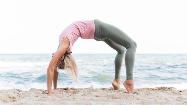 Schöne frau, die yoga am strand tut