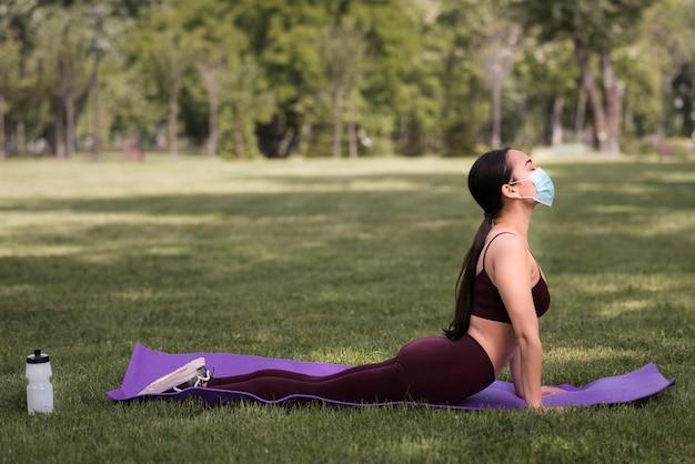 Schöne frau, die yoga draußen praktiziert