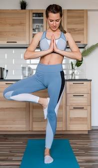Schöne frau, die yoga-haltung ausübt