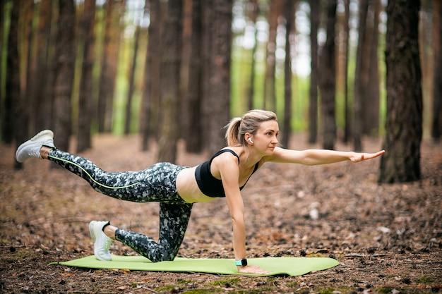 Schöne frau, die yoga im wald tut. übungs- und meditationskonzept. kiefernholz im sommerthema.