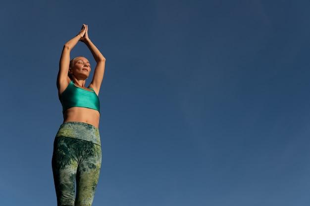 Schöne frau, die yoga tut. mittlerer plan