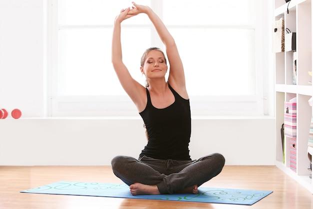 Schöne frau, die yoga-übungen zu hause macht