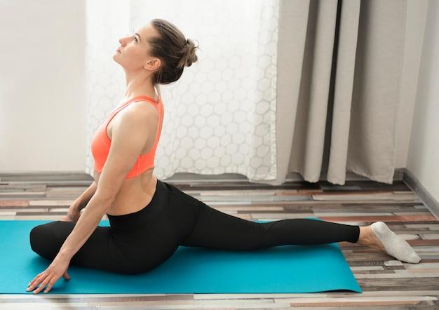 Schöne frau, die yoga zu hause praktiziert