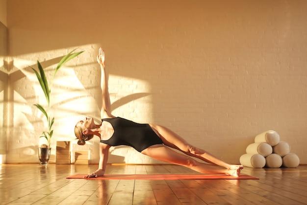Schöne frau, die yoga zur sonnenuntergangzeit tut