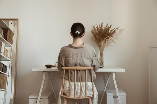 Schöne frau, die zu hause arbeitet. gemütliches, komfortables home-office-arbeitsplatz-innendesign