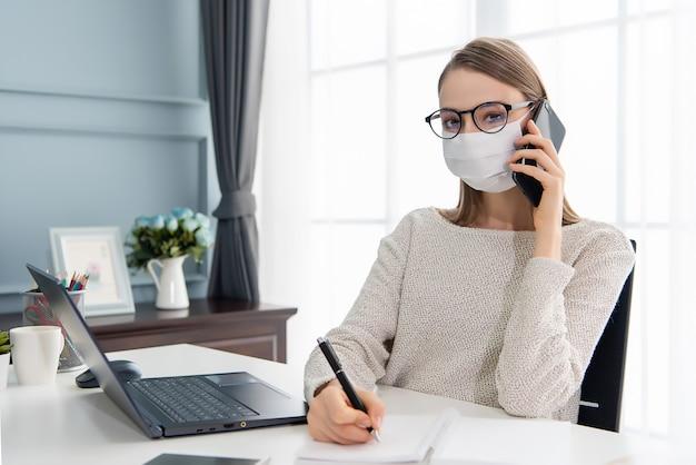 Schöne frau, die zu hause arbeitet und maske trägt
