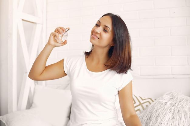 Schöne frau, die zu hause auf einem bett sitzt und parfüm verwendet