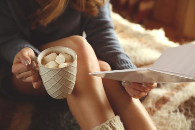 Schöne frau, die zu hause heißen kakao trinkt und buch liest
