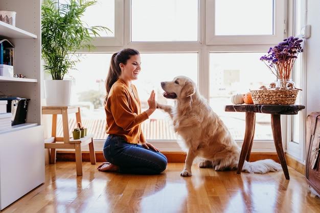 Schöne frau, die zu hause hoch fünf ihren entzückenden golden retriever-hund tut. liebe für tiere konzept. lebensstil drinnen