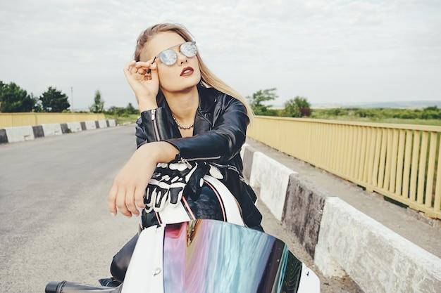 Schöne frau, die zum himmel durch die sonnenbrille sitzt auf motorrad schaut