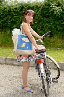 Schöne frau, die zum strand im fahrrad verlässt