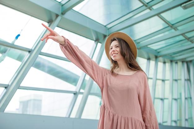 Schöne frau ein flughafenaufenthaltsraum, der auf einstieg wartet. glückliches mädchen im hut im internationalen flughafen