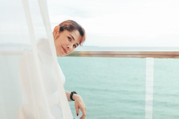 Schöne frau entspannt sich im sommer auf der hotelterrasse mit meerblick