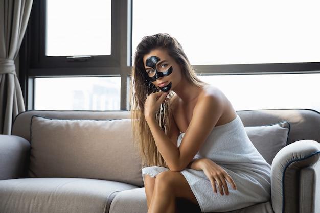 Schöne frau entspannt zu hause mit schwarzer peel-off-maske auf ihrem gesicht