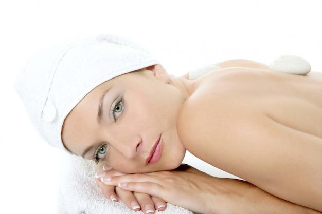 Schöne frau entspannte sich auf badekurort mit steinbehandlung