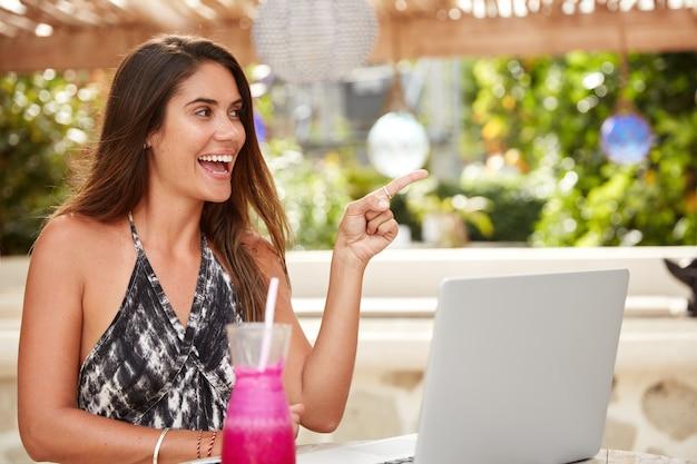 Schöne frau freiberuflerin mit langer frisur arbeitet am laptop, erledigt fernarbeit, zeigt glücklich irgendwo an, während sie in gemütlicher cafeteria mit frischem cocktail sitzt. menschen, freizeit, erholung