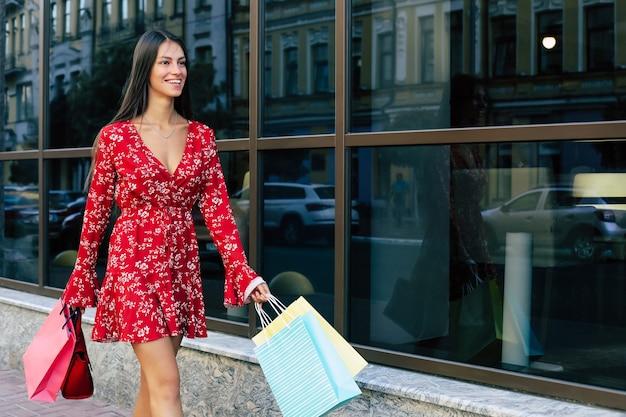 Schöne frau geht in einem roten blumenkleid die straße entlang, trägt mehrere einkaufstüten, lächelt und freut sich
