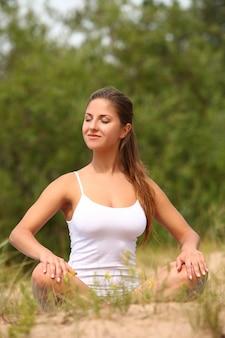 Schöne frau genießen yoga am wald