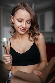 Schöne frau hält einen löffel in der küche und betrachtet das rezept in einem buch lächelnd