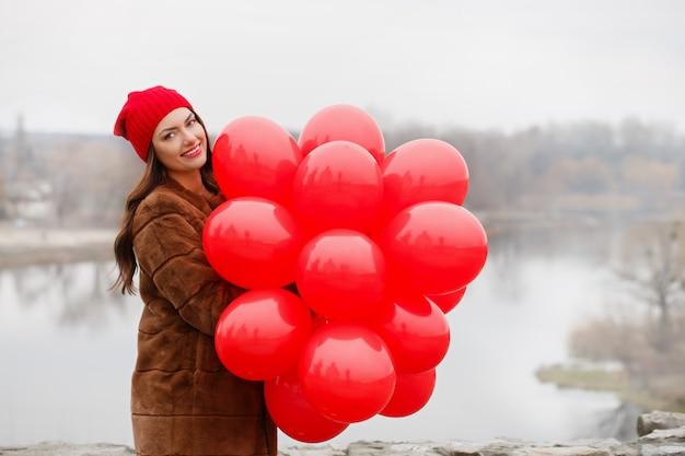 Schöne frau hält einen luftballons in ihren händen