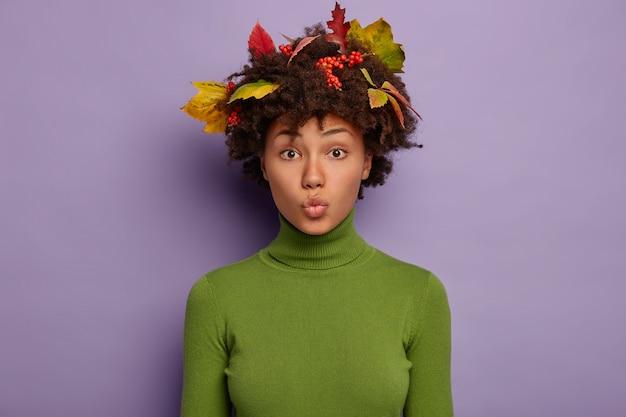 Schöne frau hält lippen gerundet, hat kurzen haarschnitt, herbstlaub im haar, trägt grünen rollkragenpullover, posiert vor lila hintergrund