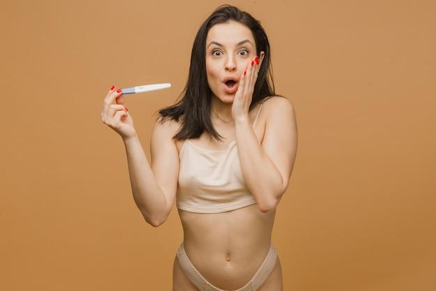 Schöne frau hält schwangerschaftstest mit geschocktem gesicht, jungem und fitem körper, der in unterwäsche aufwirft
