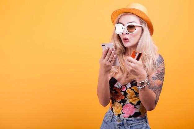 Schöne frau hält smartphone und kreditkarte im studio auf gelbem hintergrund