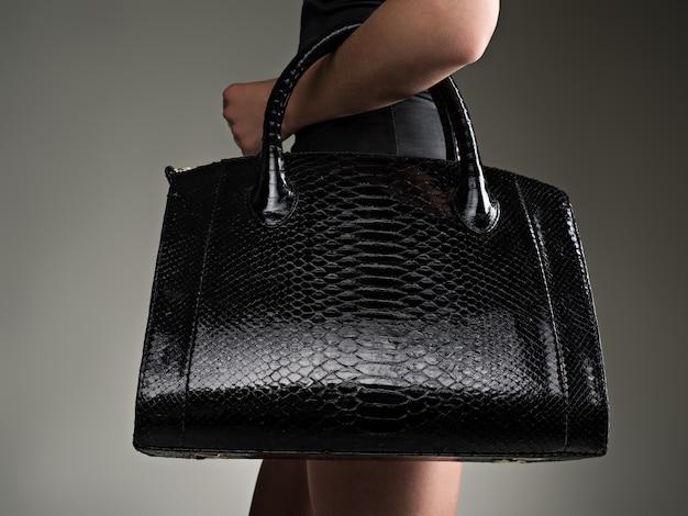 Schöne frau hält stilvolle schwarze tasche. modisches mädchen. glamour stilvolles konzept. kunst. frau nach dem einkaufen. nicht erkennbare frau.