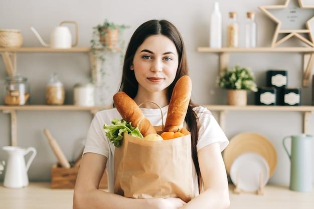 Schöne frau halten öko-einkaufstasche mit frischem gemüse in der küche