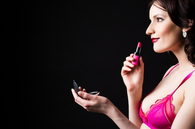 Schöne frau halten rosa lippenstift lokalisiert auf einem schwarzen hintergrund.