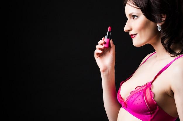 Schöne frau halten rosa lippenstift.